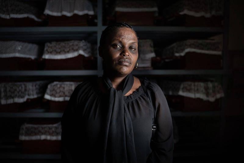 卢旺达基布耶,哥特沃偌大屠杀纪念馆,大屠杀幸存者阿尔伯蒂娜·马克卡曼姿(Albertine Mukakamanzi)在灵柩前拍照。图源:视觉中国