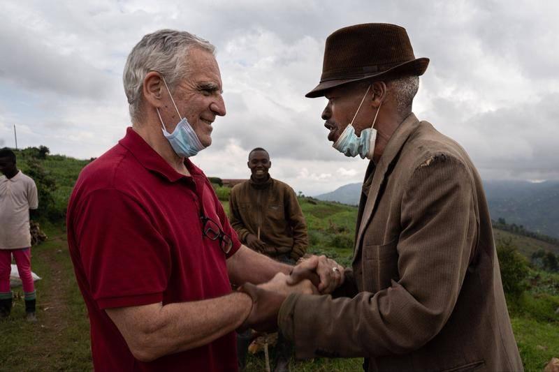 当地时间2020年12月2日,卢旺达比斯斯诺(Bisesero),大屠杀幸存者亚伦·马克米扎(Aaron Mukomeza)欢迎阿兰·戈捷(左)。图源:视觉中国